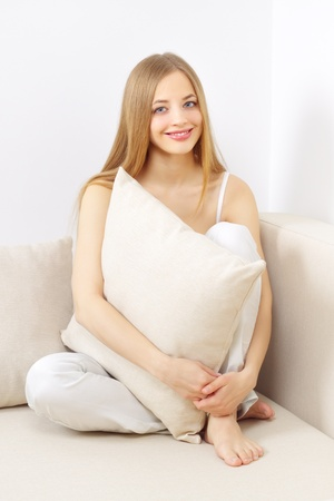 smiling girl sitting on sofa on a light background photo