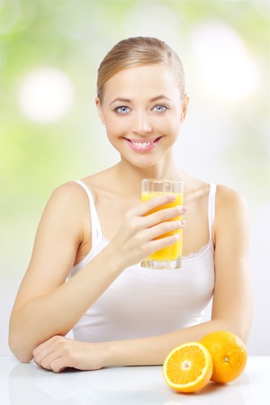Smiling girl with orange juice on a green background Stock Photo - 12235336