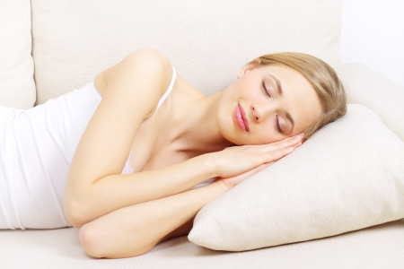 Sleeping girl on sofa on a light background Stock Photo