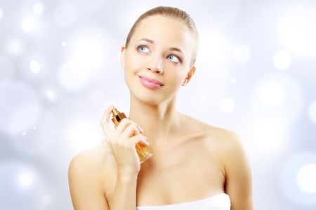 parfum: Young woman spraying perfume. on a light background