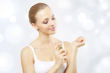 fragranza: Giovane donna spruzzare profumo. su uno sfondo chiaro