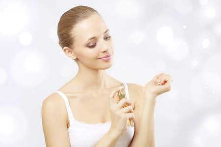 fragrance: Young woman spraying perfume. on a light background