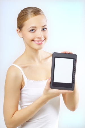 publisher: Attractive girl with the e-book reader on a light background