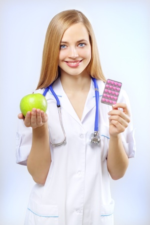 nurse holding an apple and pills on a blue background photo