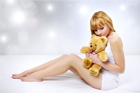 1 adult only: Attractive girl with a teddy bear on a gray background