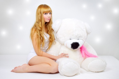Attractive girl with a teddy bear on a gray background photo