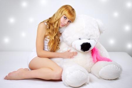 teddybear: Attractive girl with a teddy bear on a gray background