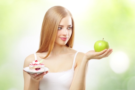 girl holding a cake and apple on a light background Stock Photo