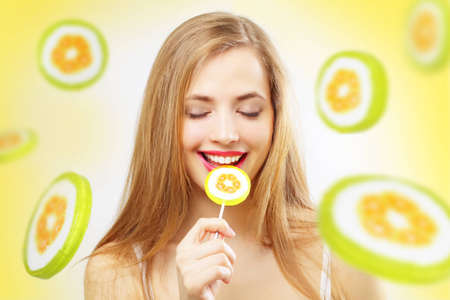 girl licking: Lollipop. Girl with lollipop on a yellow background