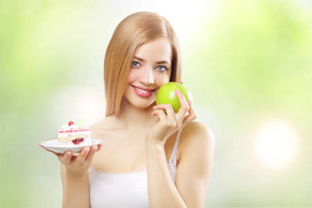 girl holding a cake and apple on a light background photo