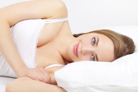 wellness sleepy: Beautiful girl lying on a bed on a light background