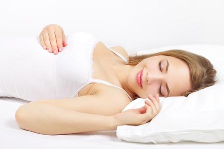 um jovem mulher só: Menina que dorme na cama no fundo claro