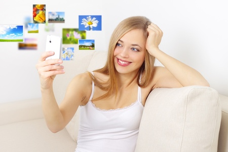girl holding a mobile phone on light background