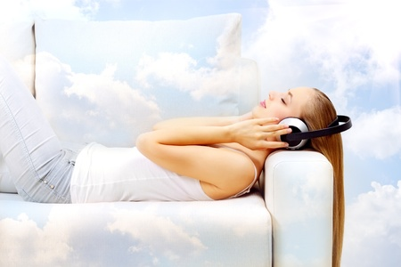 Young attractive girl lying on sofa, listening to music in the clouds photo