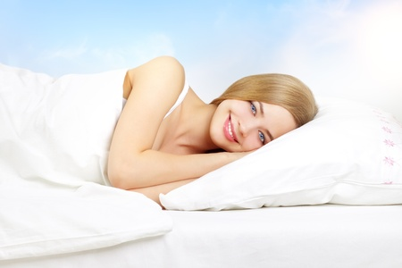 Beautiful girl lying on a bed on a light background