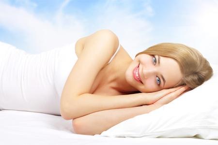 coussins: Belle fille couch�e sur un lit sur un fond clair