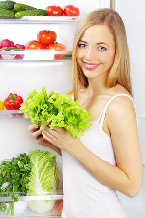 green leafy vegetables: girl with a green salad  Background of the refrigerator