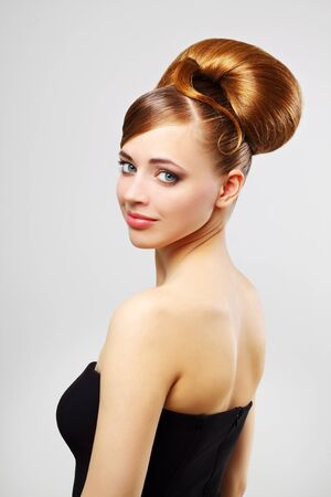 Beautiful girl with retro hairstyle on a gray background photo