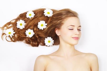Hermosa niña con flores en el pelo sobre un fondo claro