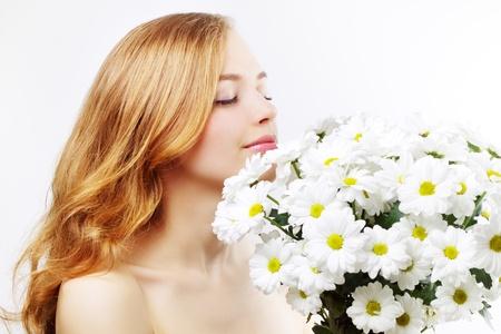 beautiful girl with white chrysanthemum on light background photo