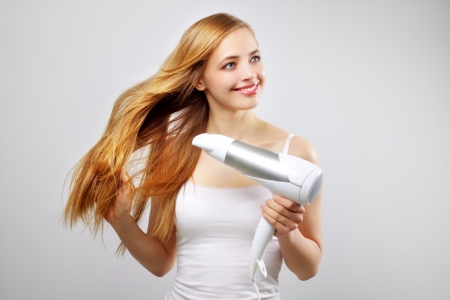 Beautiful smiling girl drying her hair with a blow dryer photo