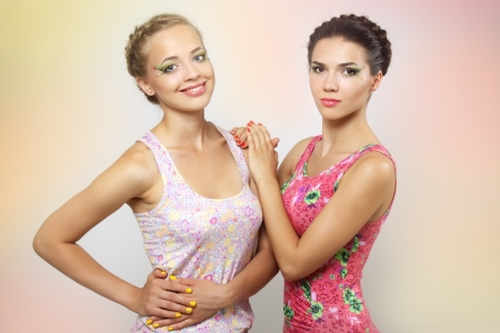 Two girls with colored make-up on a light background photo