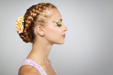 braid: Woman with beautiful hairstyle and creative make-up on light background