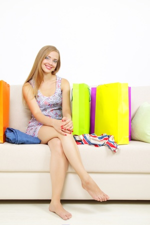 Stylish Girl with shopping bags on sofa photo