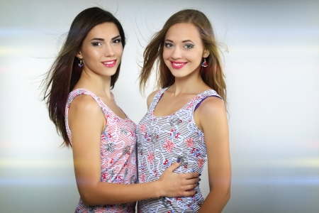 Two beautiful girls on blue background Stock Photo - 14531290