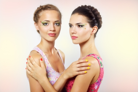 Two girls with colored make-up on light background photo