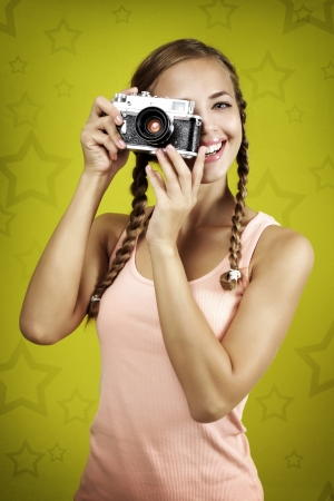 female photographer: Young girl taking photo with retro camera on yellow background Stock Photo
