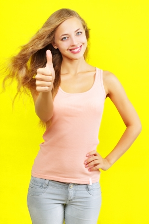 Portrait of attractive girl showing a thumbs up on yellow background