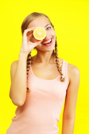 young girl holding lemons on yellow background photo