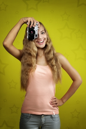 Young girl taking photo with retro camera on yellow background photo