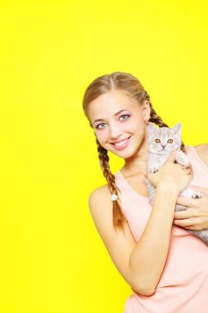 scottish straight: Smiling girl with Scottish Straight on yellow background