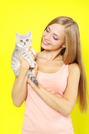 Smiling girl with Scottish Straight on yellow background photo