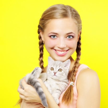 Smiling girl with Scottish kitten on yellow background photo