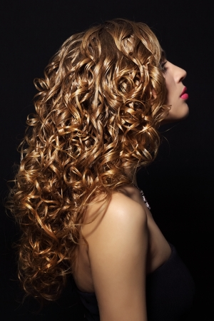 Portrait of a beautiful girl with curly hair on black background Foto de archivo