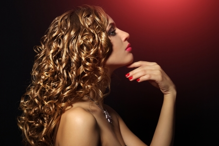 Portrait of a beautiful girl with curly hair on black background Stock Photo