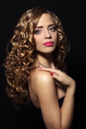 Siyah bir arka plan üzerinde kıvırcık saçlı güzel bir kızın portresi