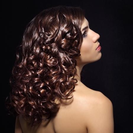 Siyah arka plan üzerinde kıvırcık saçlı güzel bir kız portresi
