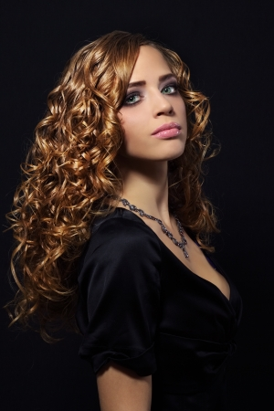 Portrait of a beautiful girl with curly hair on black background Stock Photo - 16141687