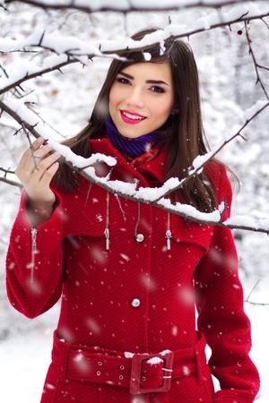 Beautiful elegant woman in red coat  winter nature Foto de archivo