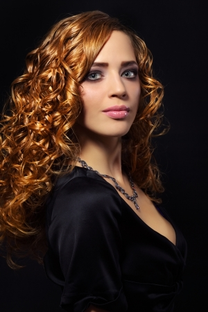 Portrait of a beautiful girl with curly hair on black background Stock Photo - 16237437