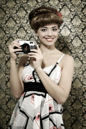 Retro style  Smiling girl with camera on dark background photo