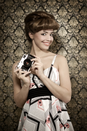 Pin up girl with retro camera on dark background photo
