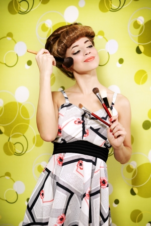 Retro style  Beautiful girl with makeup brushes photo
