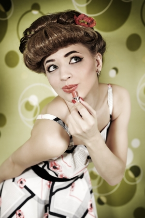 Pin-up girl with lipstick on light background photo