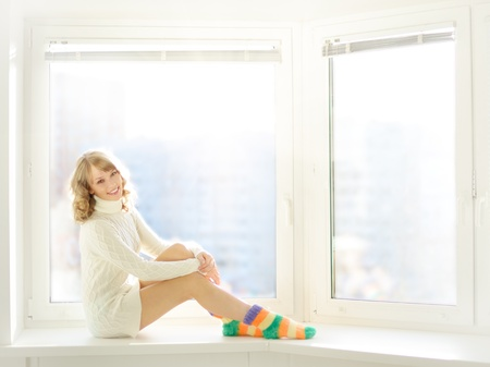 Beautiful girl sitting at the window photo