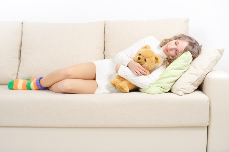 Girl resting on the couch on light background photo